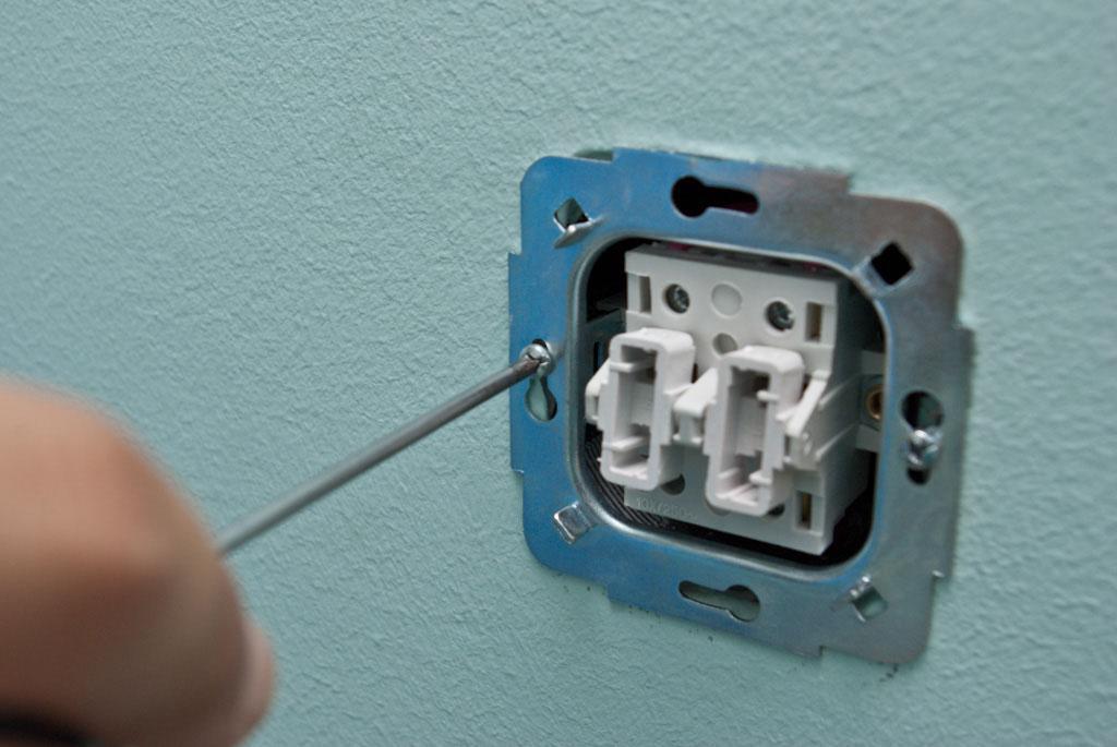Прикручиваем основание выключателя к стене