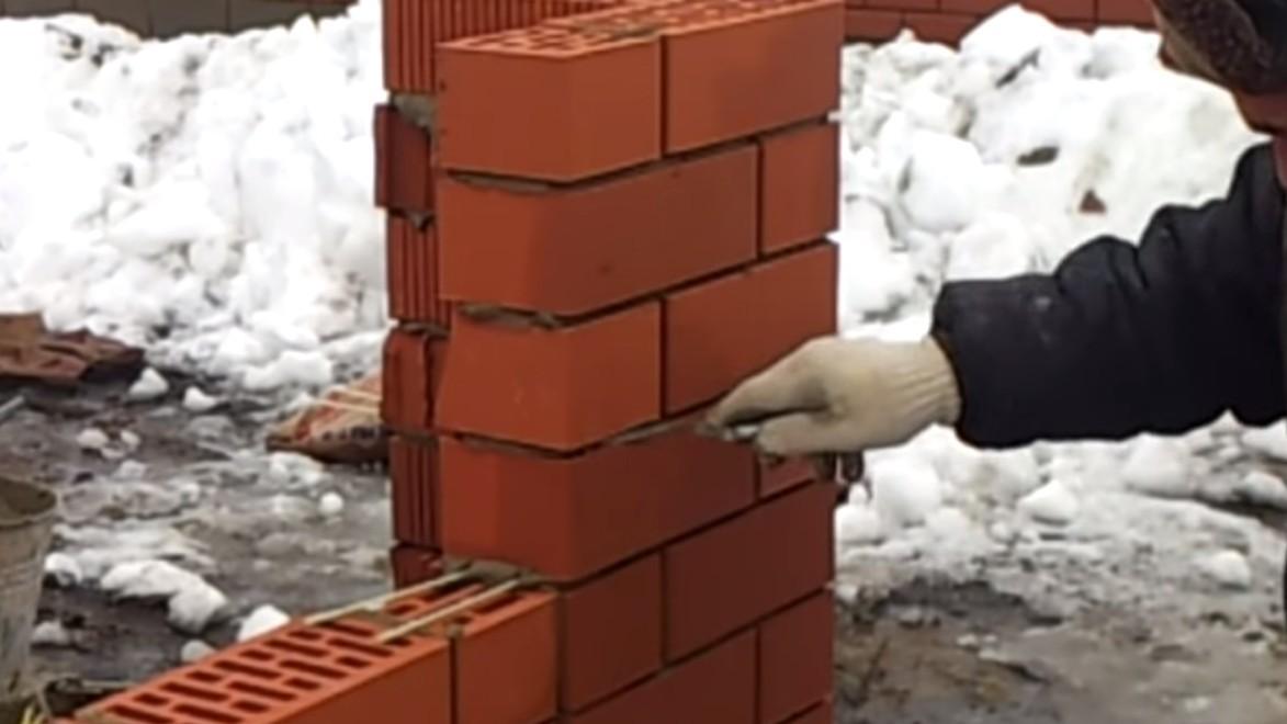 строится стена из кирпича